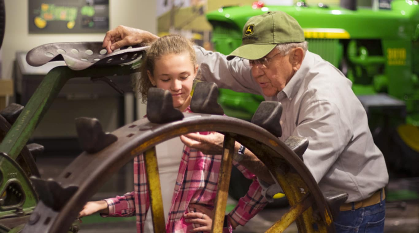 A man and his granddaughter inspect the wheel of a vintage tractor
