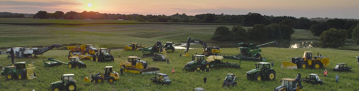 People walking amongst several types of John Deere equipment in a large field.