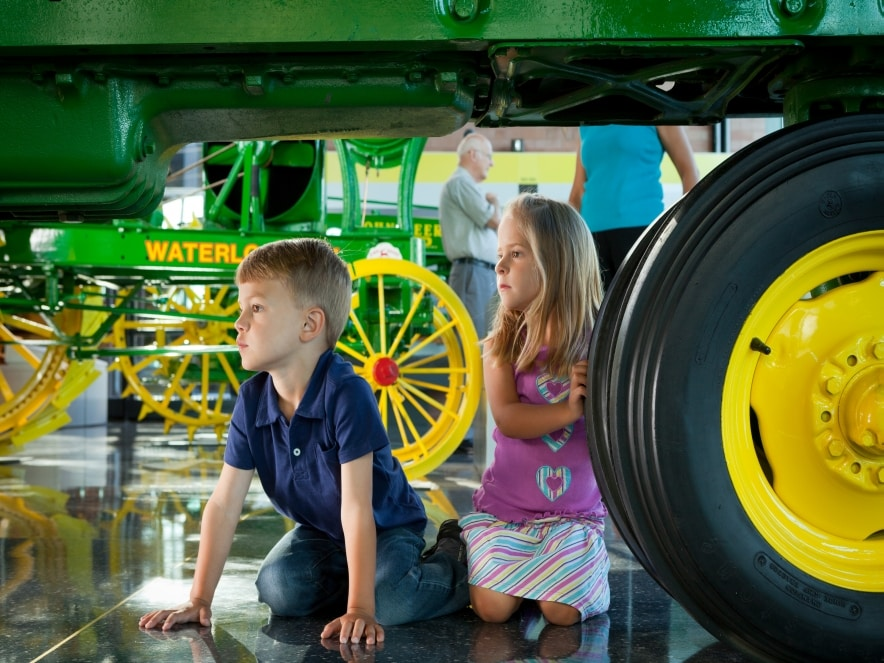 Two children explore and exhibit at the John Deere Tractor & Engine Museum
