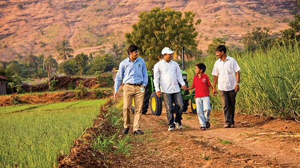 Three men and one little boy walking on the fields