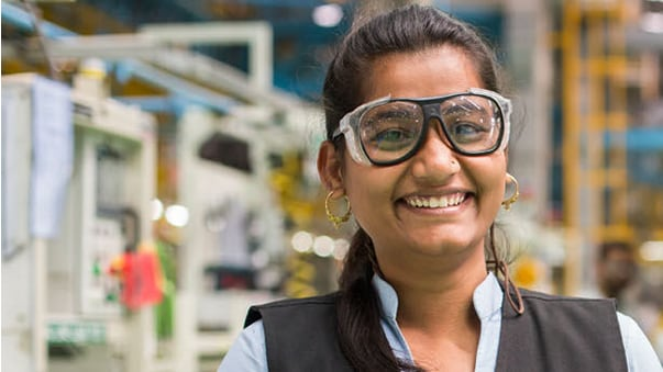 A smiling Indian girl wearing safety glasses in John Deere lab